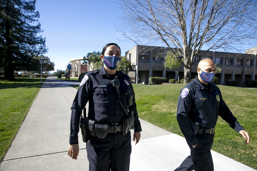 Campus police officers Tejinder Arurkar, left, and Lt. Omar Miakhail walk around the Cal State East Bay campus in Hayward on Feb. 17, 2021. CSUEB has one of the most diverse campus police departments in the state. Photo by Anne Wernikoff, CalMatters
