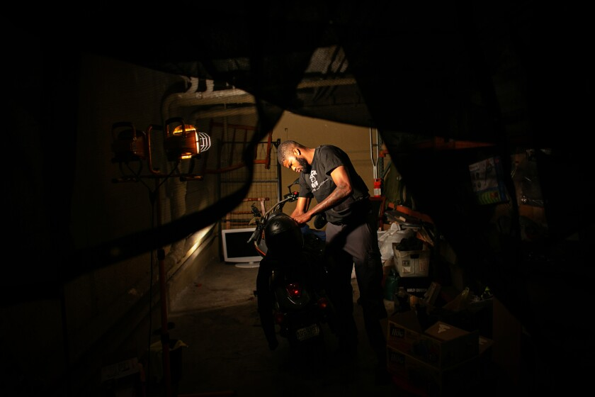A man in a shadowed garage leans over a motorcycle.