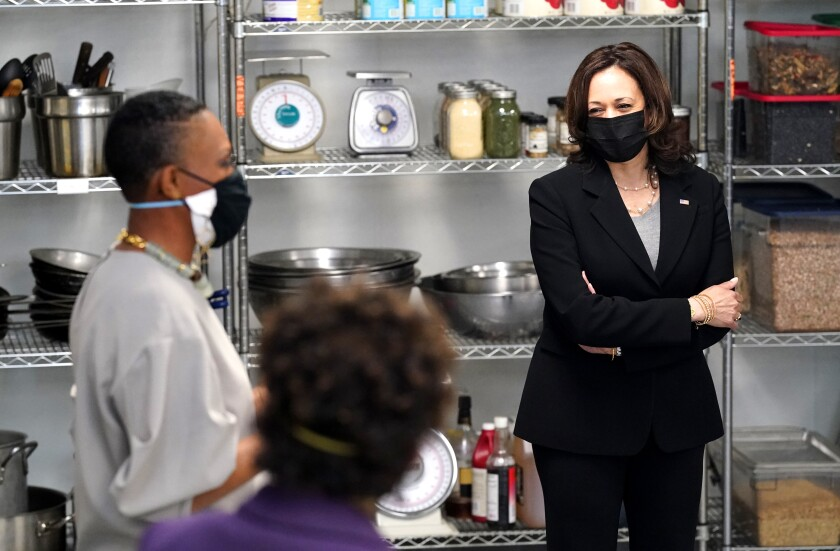 Vice President Kamala Harris stands with arms folded near two people with shelves of food and kitchen equipment behind them.