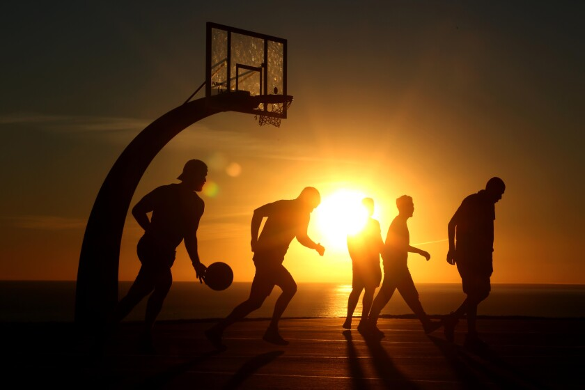Basketball players are silhouetted against a setting sun