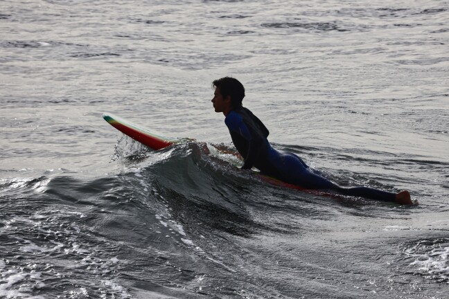 Getting on a surfboard.