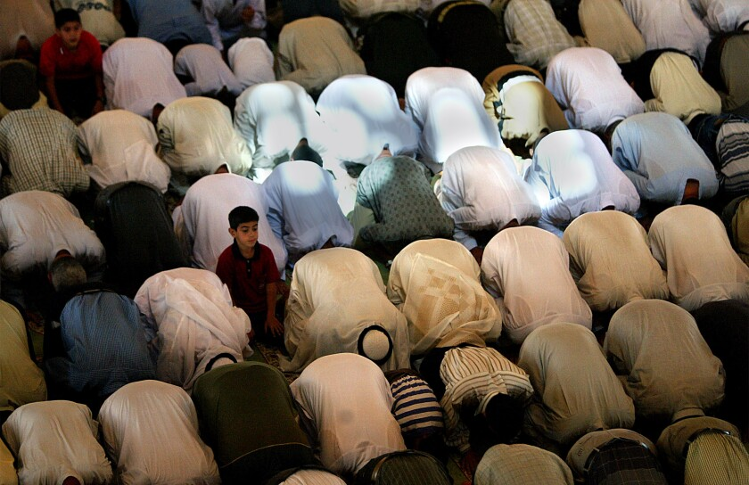 A boy sits up amid rows of people bowed over on the floor in prayer
