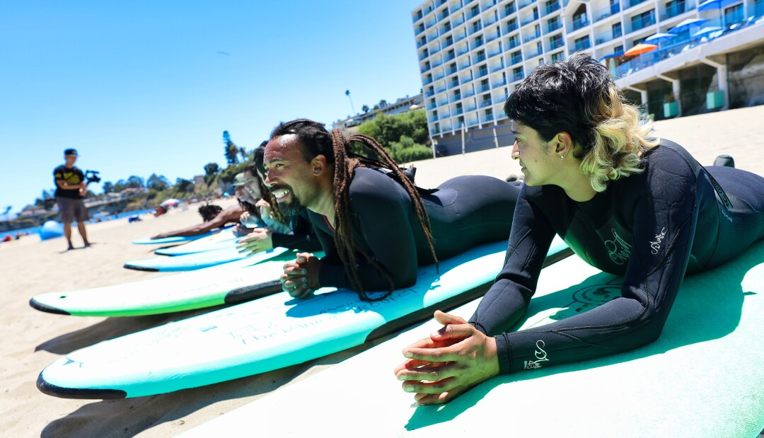 Surfers prepare ahead of the Black Surf Club Santa Cruz paddle-out Sunday.