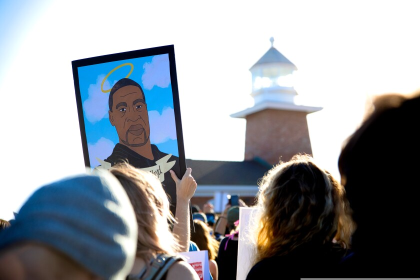 A protester holds up a painting of George Floyd during a police brutality protest near Lighthouse Point