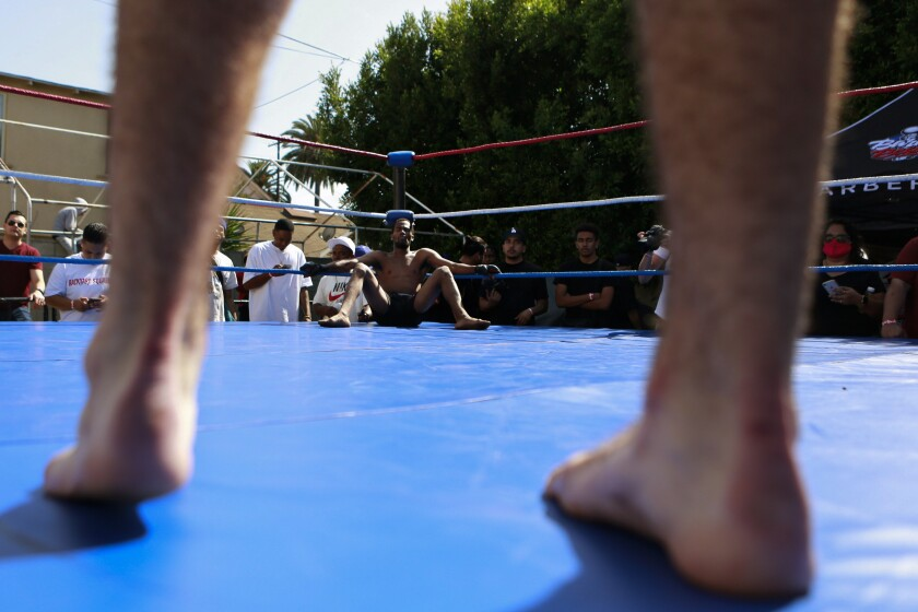 A man sits in a boxing ring, viewed through the bare legs of his opponent.
