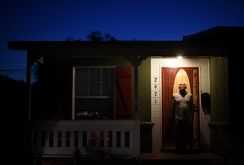 Surfer Bob Levy poses outside his house in Long Beach.