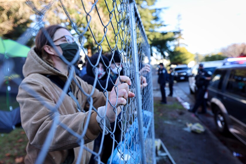 Protestors hold up a fence in an effort to block Santa Cruz police officers from entering San Lorenzo Park