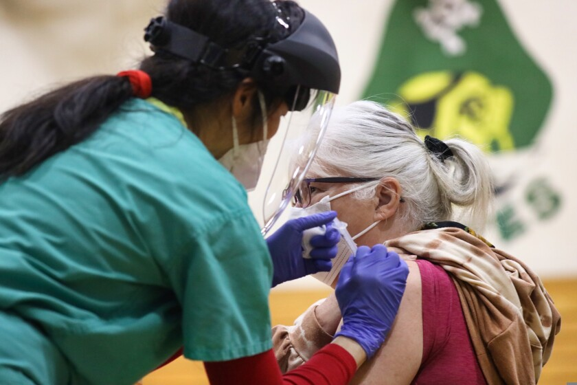 A medical team member of Dignity Health administers a COVID-19 vaccine to Jeanne Johnson on Thursday, Feb. 11.
