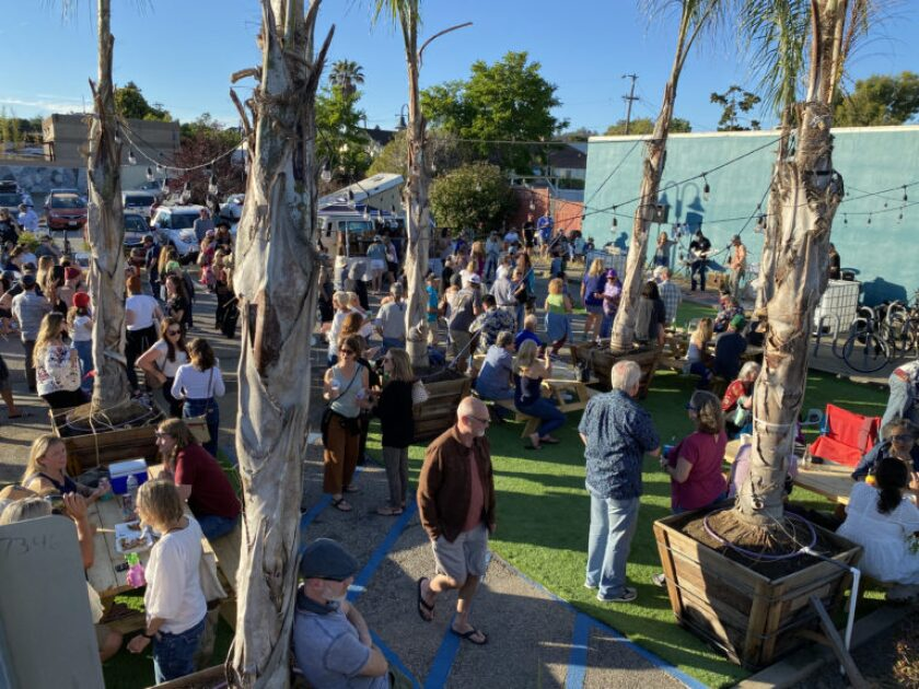 Event goers take in the music at Midtown Fridays in the City owned parking lot at 1111Soquel Avenue.