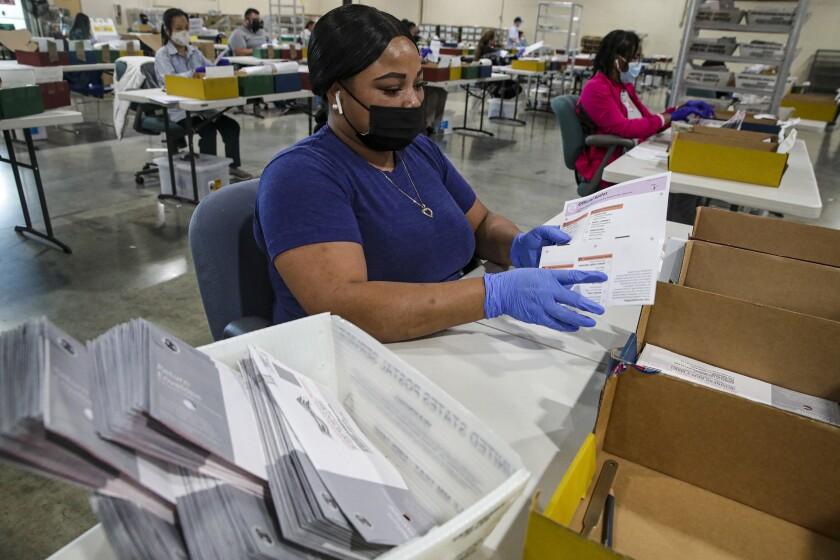 An election worker inspects a ballot