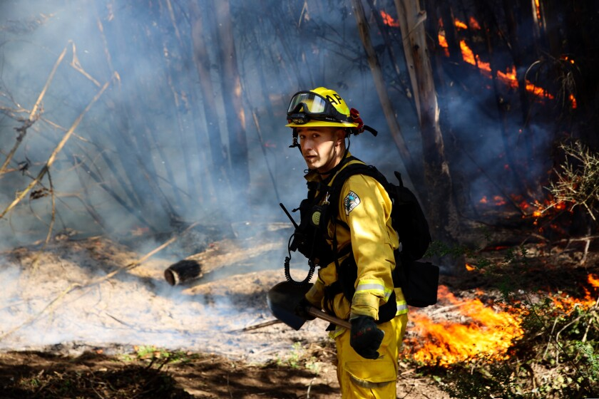 Firefighters from Aptos fire work to put out a blaze off of Gillette Rd. in Watsonville on Tuesday afternoon.
