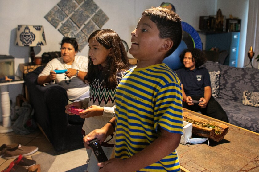 Luz Puebla and her children play video games together in South Gate.