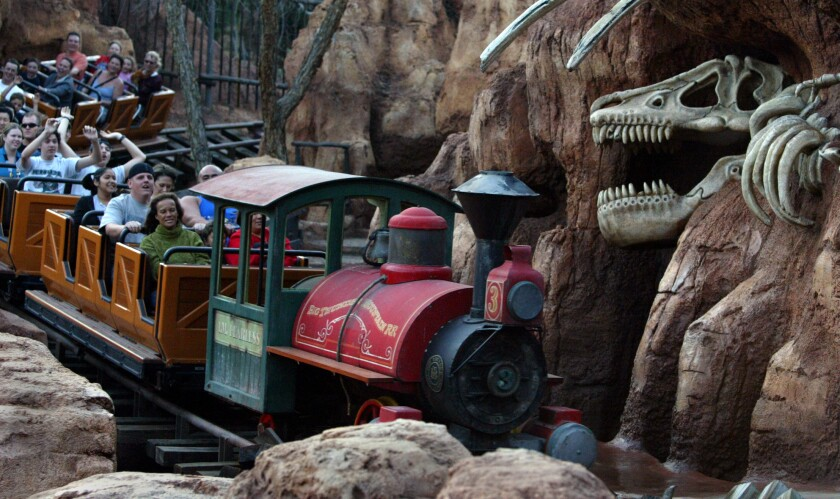 Riders on a roller coaster with a train motif
