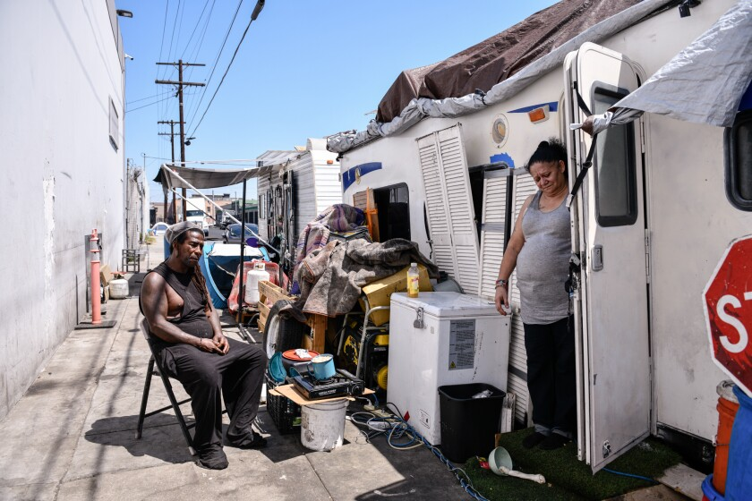 Rafael Suarez and April Lei linger outside their trailer home to try and stay cool during a hot day in Los Angeles, on July 9, 2021. The couple have lived on this block for a year and a half, according to the couple. Pablo Unzueta for CalMatters