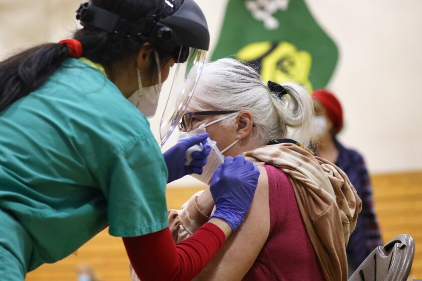 A woman is vaccinated at a Harbor High clinic.