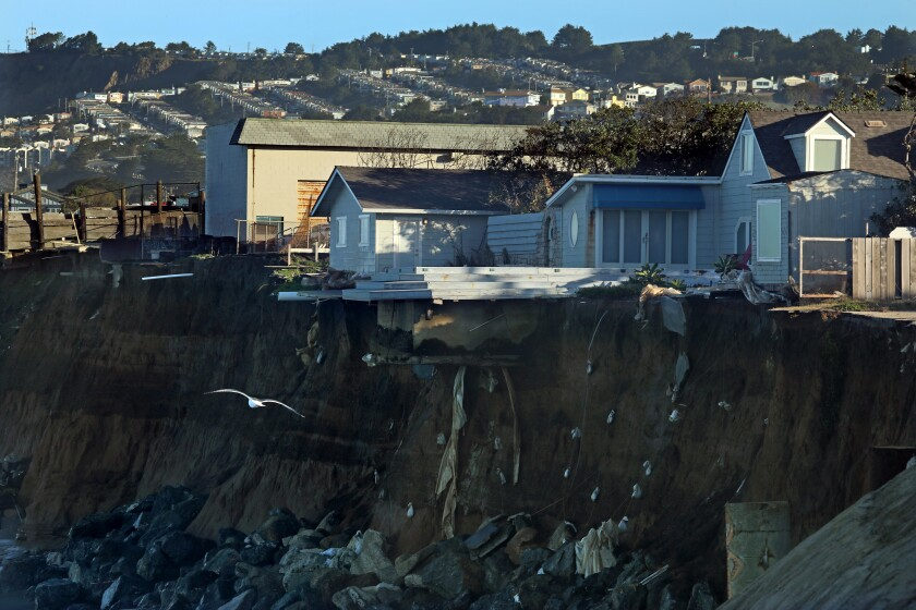 Homes dangle on the edge of a seaside cliff in Pacifica.