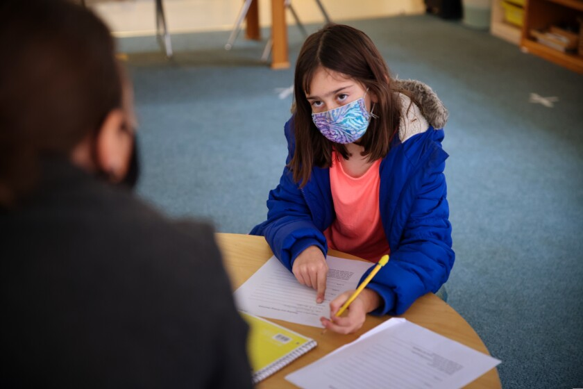 A child in a mask does schoolwork