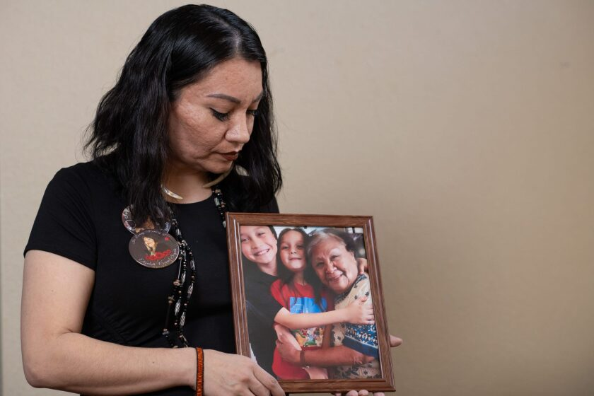 Leticia Aguilar poses for a portrait holding a picture of her grandmother