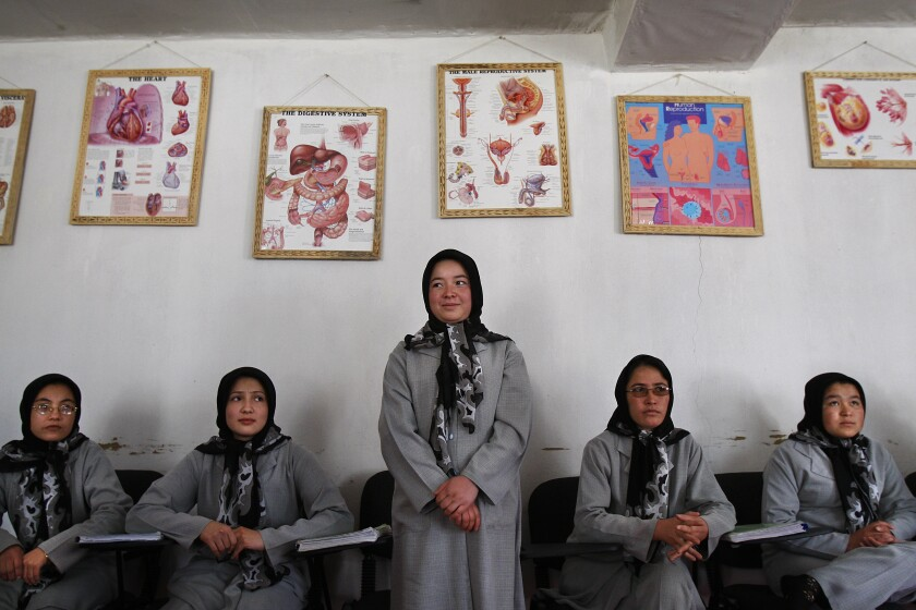 A young woman in a headscarf and gray uniform stands with four other women seated around her