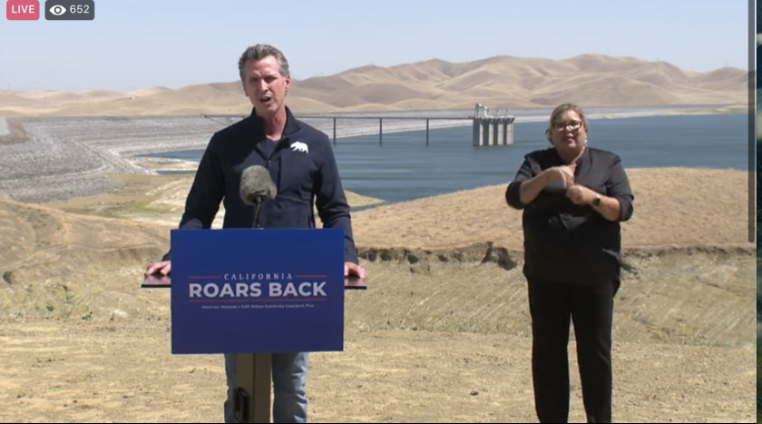 Gov. Gavin Newsom speaks about the drought on Monday, in front of the half-empty San Luis reservoir in Merced County.