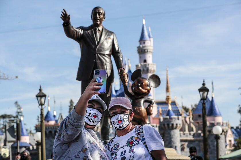 ANAHEIM CA APRIL 30, 2021 - Park visitors take a selfie in front of the Walt Disney statue inside Disneyland as the theme park reopens for the first time in more than a year on Friday, April 30, 2021.(Robert Gauthier / Los Angeles Times)