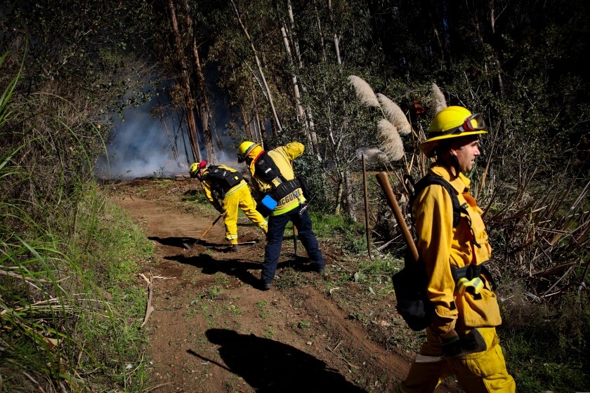 Firefighters from the Aptos Fire Department work to put out a blaze off of Gillette Road in Watsonville on Tuesday afternoon.