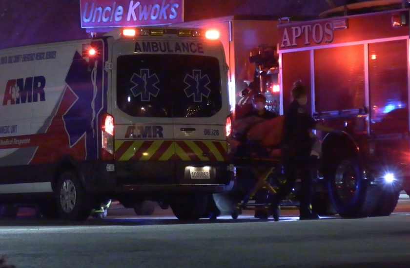 Emergency personnel load the suspect shot late Tuesday night by sheriff's deputies into an ambulance.