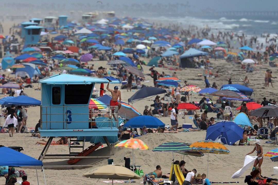 A life guard keeps watch on the crowd of people on Tuesday, June 15, 2021 in Huntington Beach