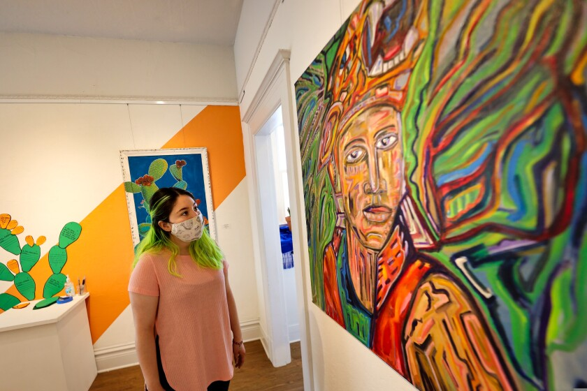PVA gallery coordinator Bianca Jimenez with exhibit artwork.