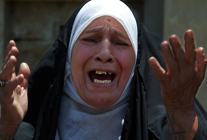 A woman in a hijab raises her hands and cries