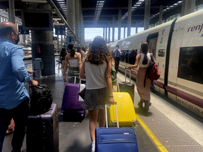 Tourists arrive at a train station in Malaga, Spain.