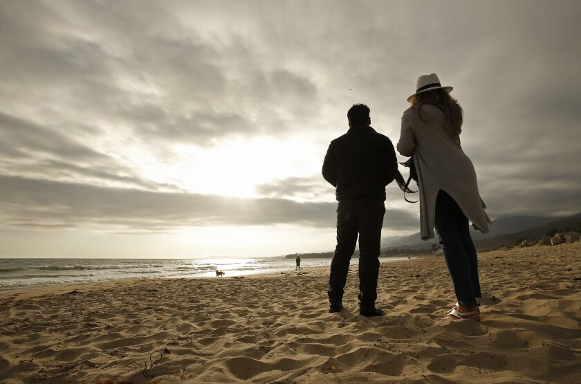 Photographer Carlos Gauna stands with his wife, Andressa, on a beach.