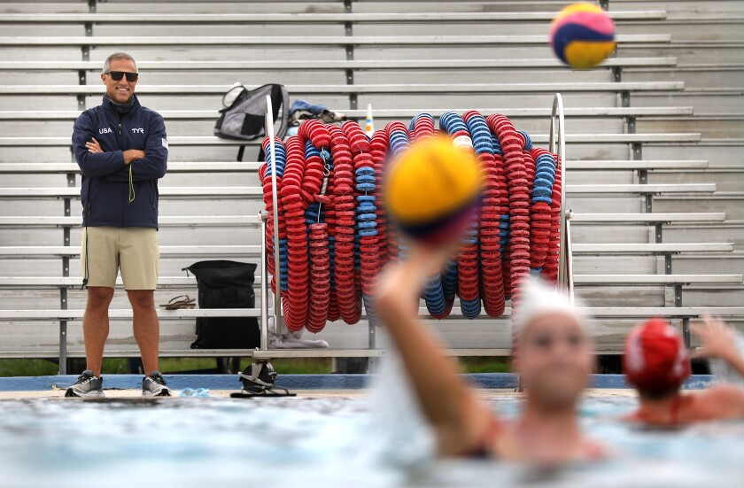 U.S. women's Olympic water polo coach Adam Krikorian watches his players from beside the pool.