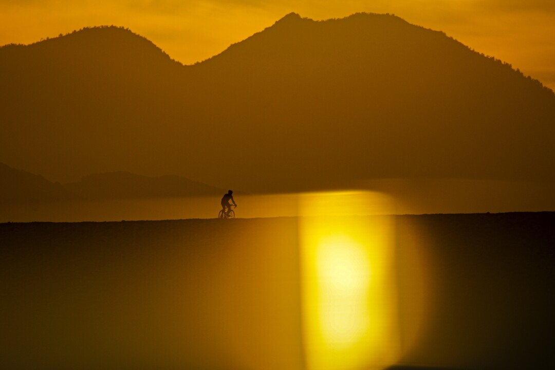Sunrise over hills and a lone cyclist in silhouette