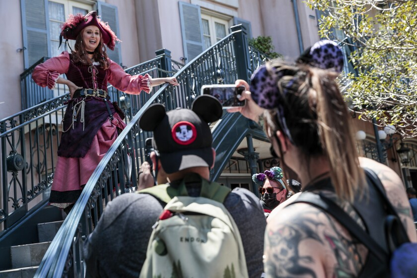 A woman in a pirate costume chatting with mouse-eared guests at Disneyland