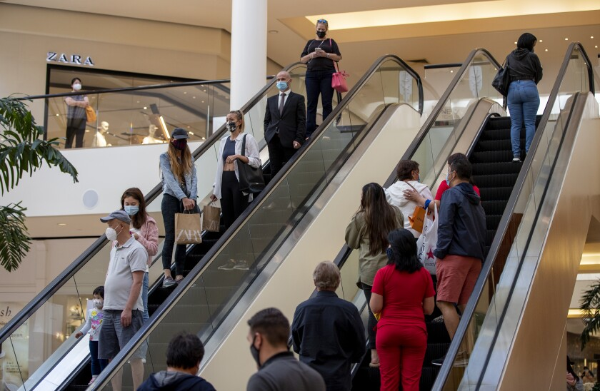 COSTA MESA, CA - MAY 13, 2021: Shoppers continue to wear masks inside South Coast Plaza on May 13, 2021 in Costa Mesa, California. Even though, the CDC announced Thursday that masked are no longer required for fully vaccinated people, the mall is still requiring masks indoors.(Gina Ferazzi / Los Angeles Times)
