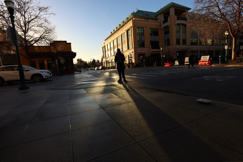 A man stands at an intersection on Pacific Avenue in Downtown Santa Cruz.