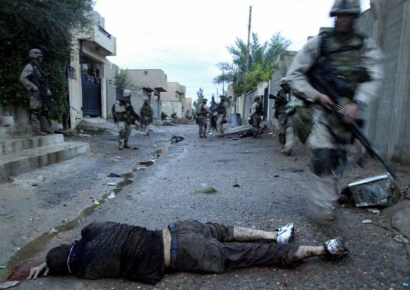 A dead man lies in the road as Marines walk past the body