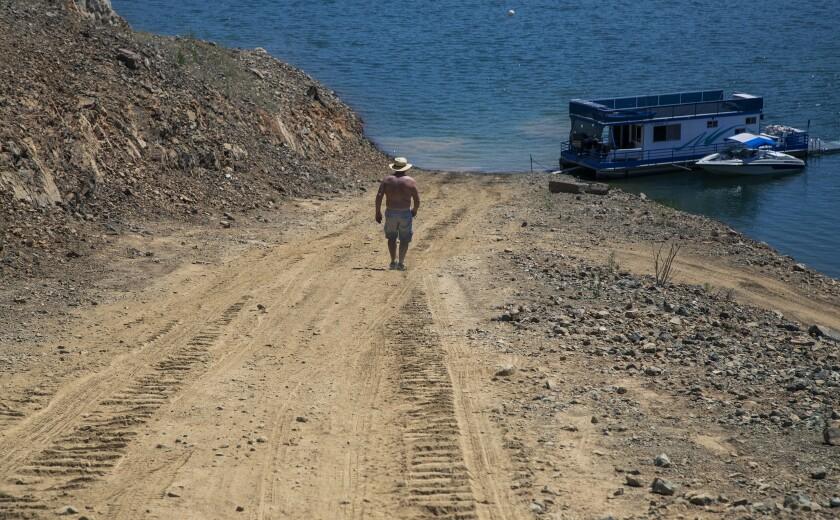 A man walks down a dry ramp, hundreds of feet from the former shoreline marina at Trinity Lake.
