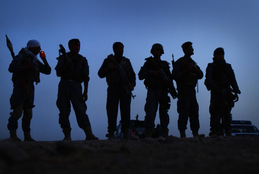 A line of armed officers silhouetted in the dawn