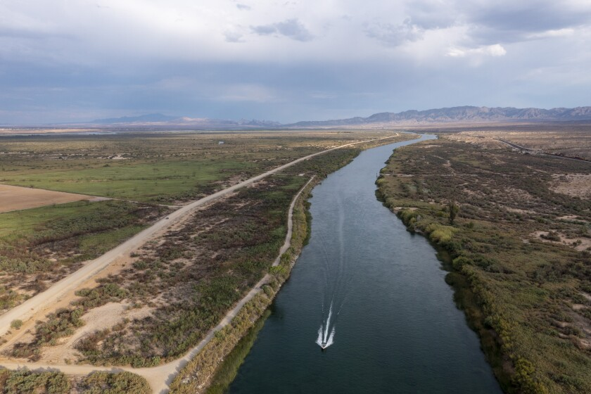 The Colorado River flows through the Mojave desert on the border of California, right, and Arizona, left, in Needles, Calif.