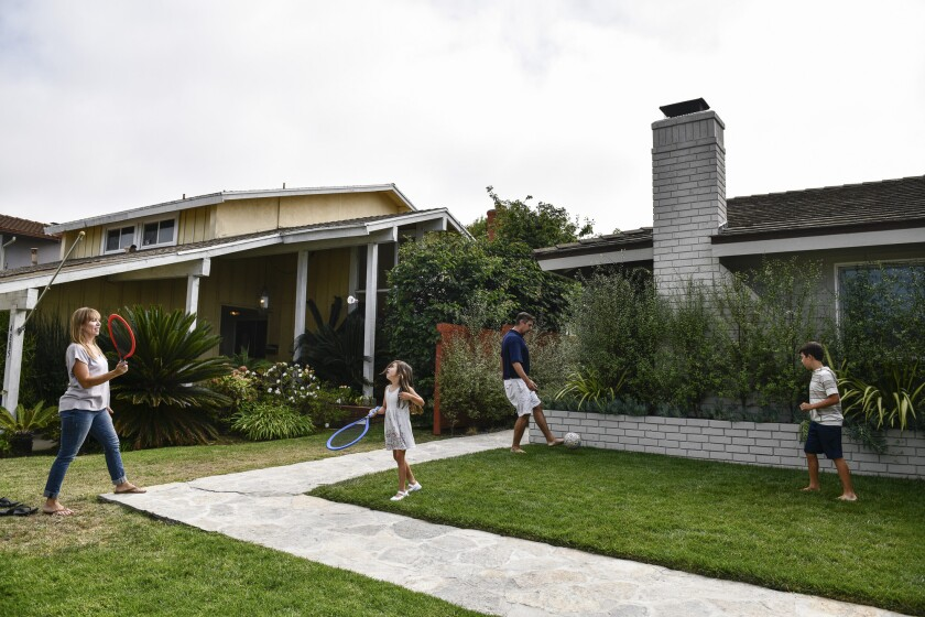 Cynthia Rojas and Kevin Jardim play with their kids in the front yard of their Culver City home