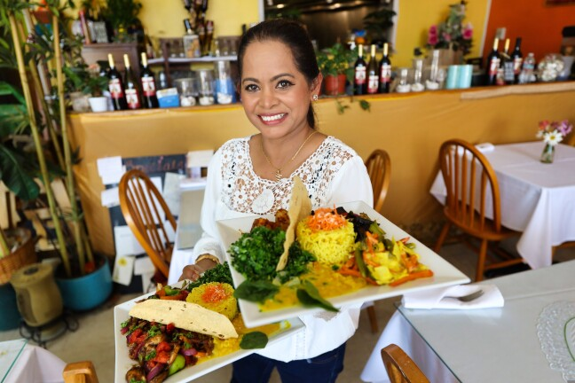 Owner Ayoma Wilen shows off some of Pearl of the Ocean's signature dishes.
