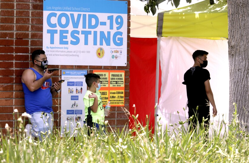 A father waits with his son to be tested for COVID-19 at Northridge Middle School