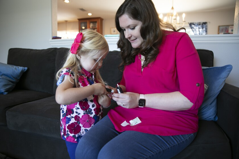 Noelle Tuominen helps Eleanor, 4, test her blood glucose levels at their Livermore home.