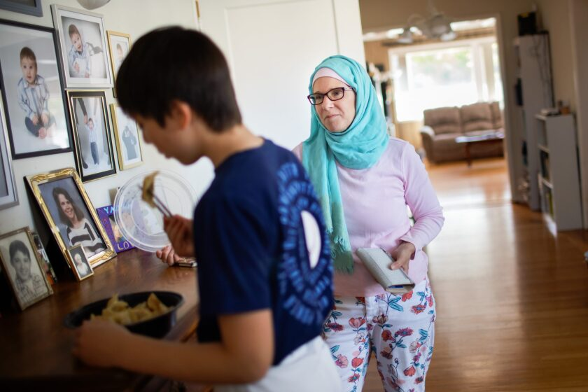 Wendy al-Mukdad talks to her son, Yazan, as he quickly eats some potstickers before his baseball practice.