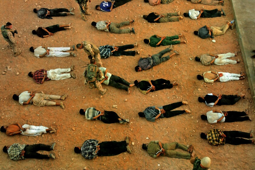 Rows of men lying face down in the dirt with their hands tied behind their backs