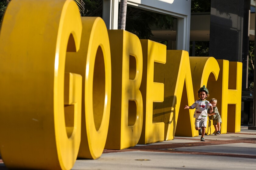 """Two toddlers run next to giant yellow """"GO BEACH"""" letters"""