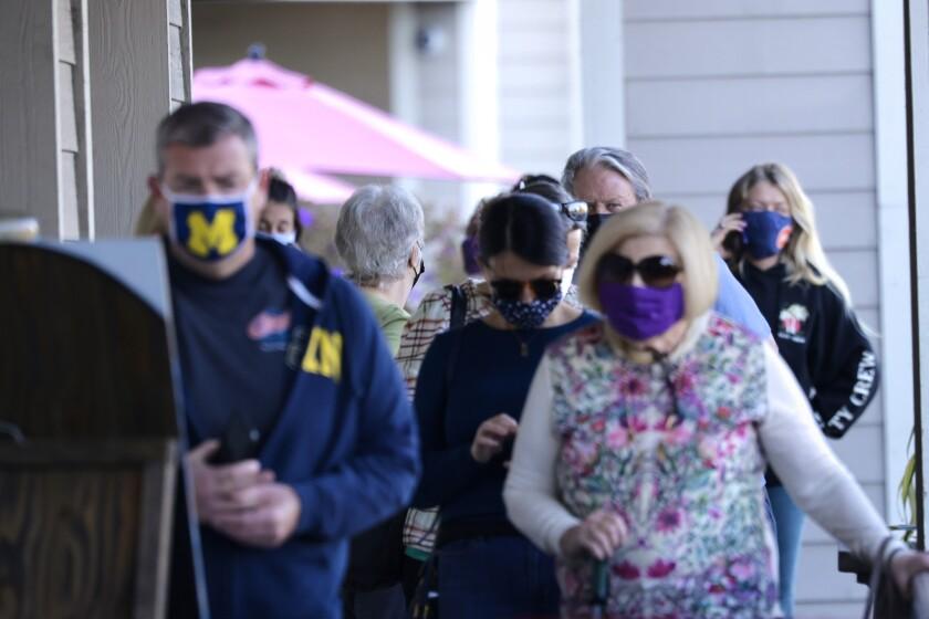 Santa Cruz residents wait in lines outside stores.