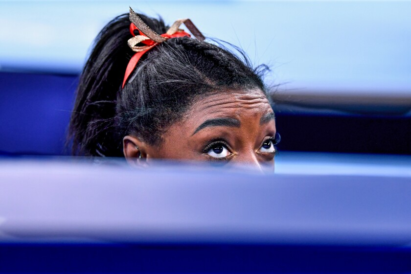 USA's Simone Biles peaks over the wall to see her score after competing on the beam